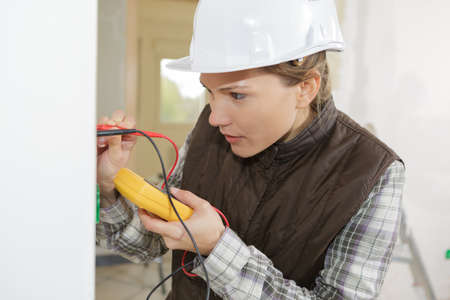 female electrician testing a wall socket Stock Photo