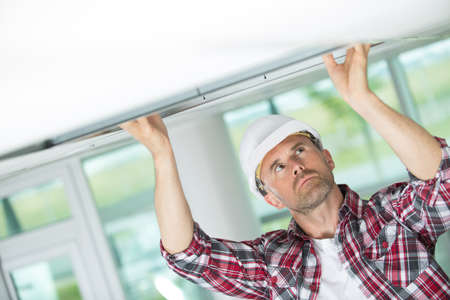 male construction worker adjusting ceiling part