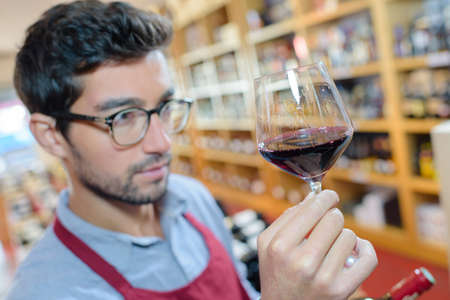 Man in apron examining glass of red wine