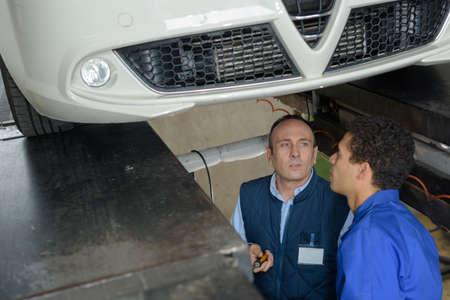 車の下で働く男性自動車修理工