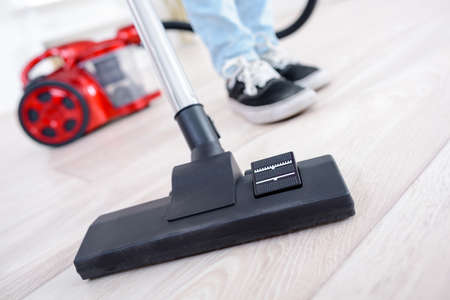 woman using vacuum cleaner in the living room Stock Photo