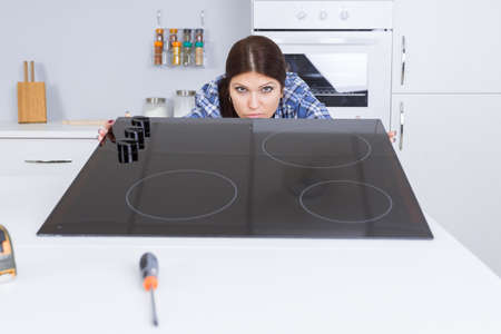 hobs: young woman technician installing induction hobs at clients home