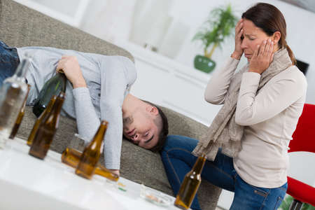inebriated: Distraught mother finding son passed out from alcohol Stock Photo