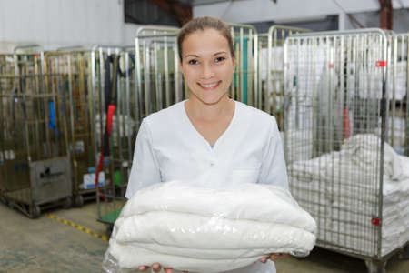 delivery service: Woman holding wrapped clean laundry Stock Photo