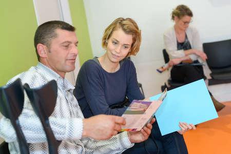 Paar die pamflet in medische wachtkamer bekijken Stockfoto
