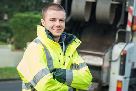 young municipal garbage collector near garbage truck Stock Photo