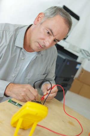 Technician using multimeter