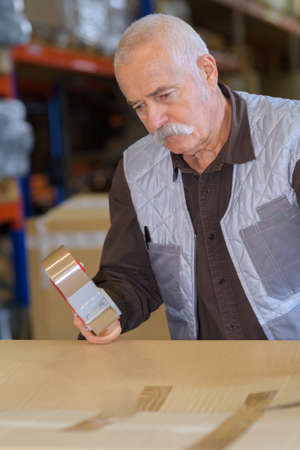 Senior man sealing cardboard box with a tape dispenser Stock Photo