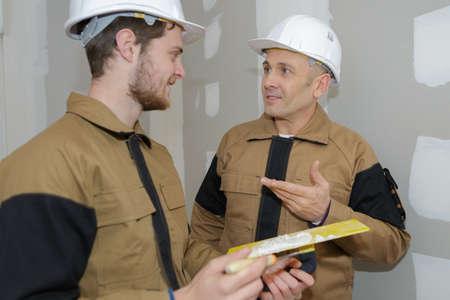 Workman instructing trainee holding trowell Stock Photo