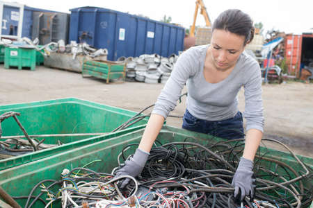 salvage yard: Woman at container of cables in salvage yard