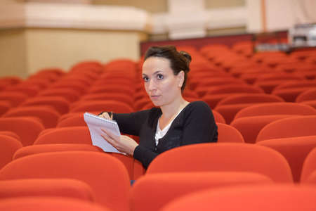 Lady with notebook in empty theatre seat
