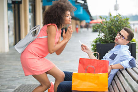 Woman begging partner for credit card while out shopping Stock Photo