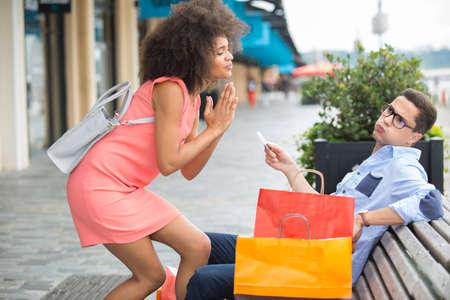 Frau bittet Partner für Kreditkarte beim Einkaufen