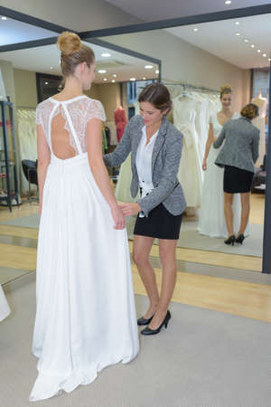 woman mirror: Woman having wedding dress fitting