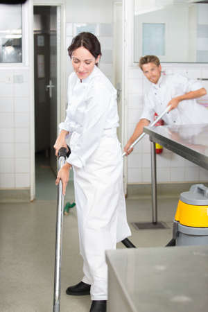 Man and woman cleaning floor in profesional kitchen