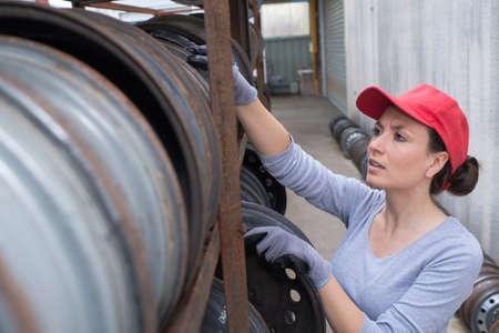 Woman looking at wheel rims in racking