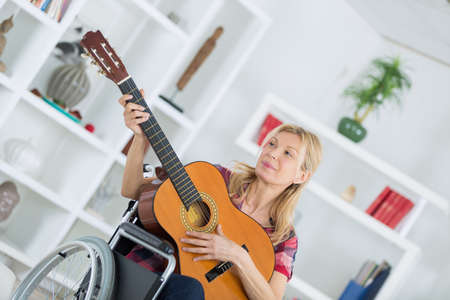 Disabled lady playing accoustic guitar Stock Photo