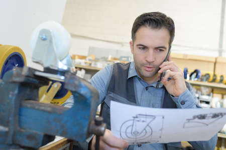questions: Man on telephone while looking at sketch of product