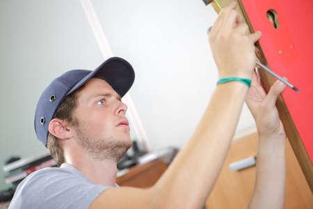 door handle: young carpenter fixing a lock door with a screwdriver