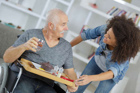 female caretaker serving breakfast to senior man at nursing home Stock Photo
