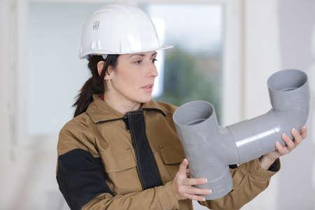 female builder holding pipe