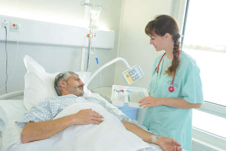 male patient lying in a hospital bed while nurse checking