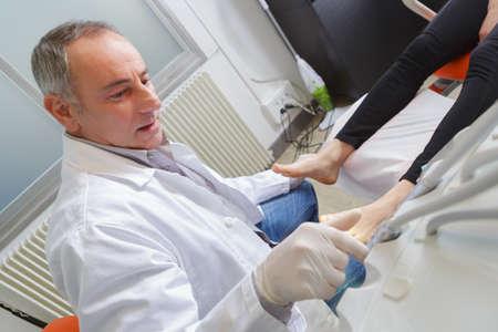여자는 gloved podiatrist에서 발 시험을 받는다. 스톡 콘텐츠