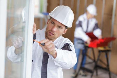 construction worker installing window in house Standard-Bild
