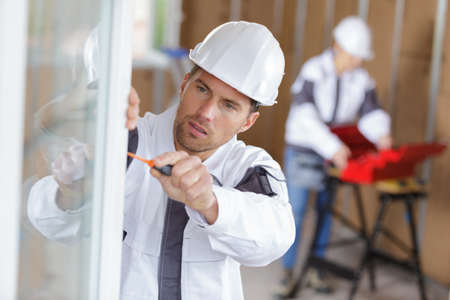 construction worker installing window in house Banque d'images
