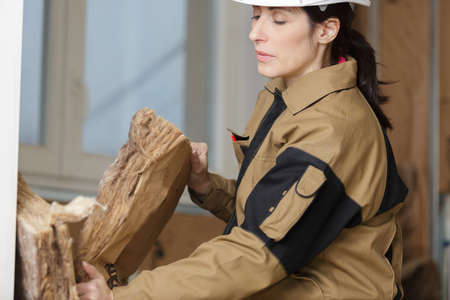 female worker using insulation  sheets at construction site