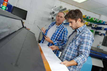 workers on offset printing machine in print factory Stock Photo
