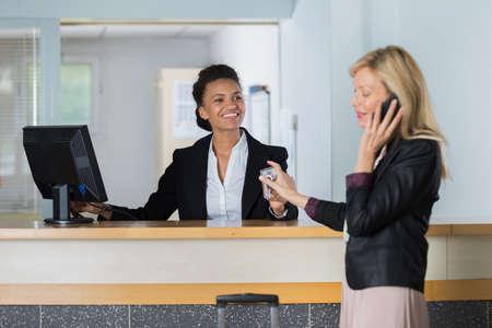 friendly hotel receptionist handing over key to customer Stock Photo