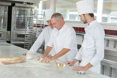 baker and assistants in a bakery kitchen Stock Photo