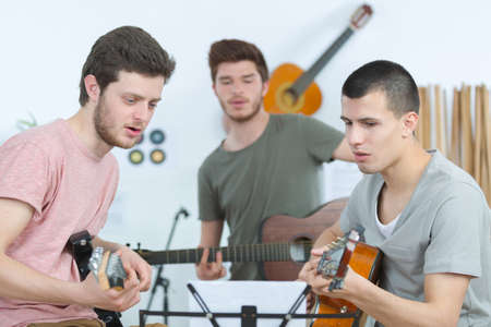 conceived: happy friends playing guitar and listening to music at home