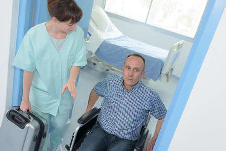 nurse helping a disabled man in wheelchair