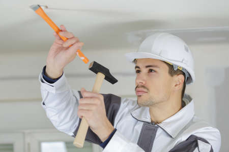 young worker making hole in ceiling for light spot