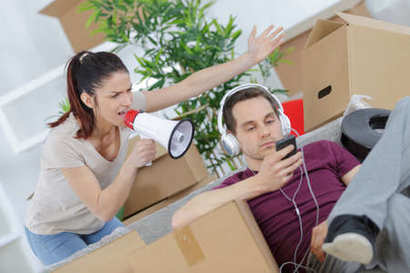 man online while angry woman calling him through a megaphone