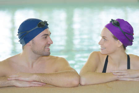 young couple of swimmers inside swimming pool Stock Photo