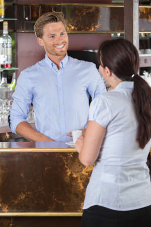 male barista flirting with female client at counter Stock Photo