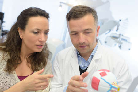 ophthalmologist showing an eye model to female customer