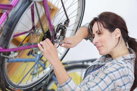 woman repairing bicycle wheel