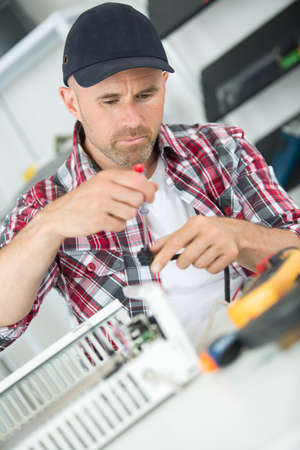 young repairman in overall repairing appliances