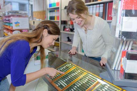 female customer choosing a pencil or pen