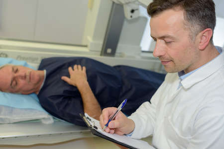 old man lying in hospital bed while doctor doing notes