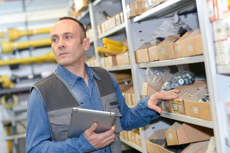 warehouse worker checking supplies in a tablet computer