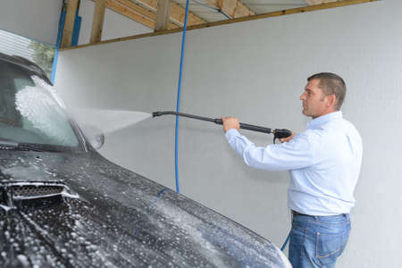 garage: man cleaning a car using spray water