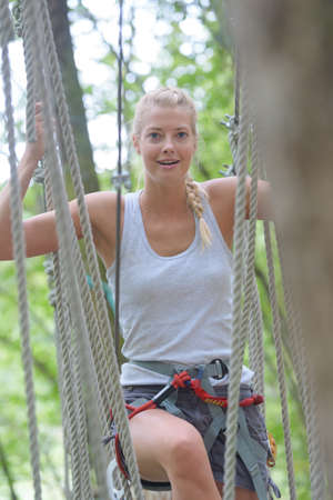cute girl climbing in a rope at adventure park Stock Photo