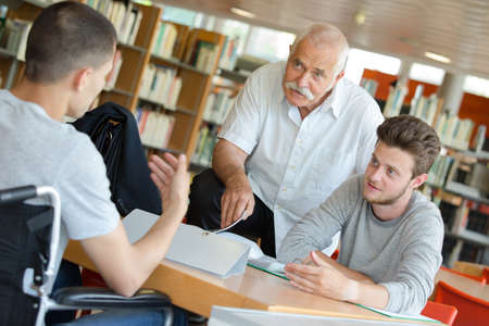male student in wheelchair in a library Stock Photo