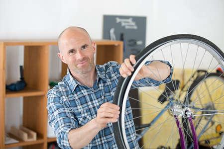 man fixing wheel in his workshop Imagens - 85951109