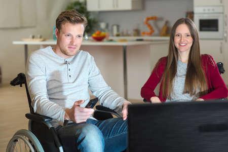 boy on wheelchair watching tv with girlfriend Stock Photo